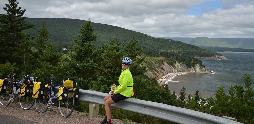 Woman sitting on guardrail with touring bike overlooking ocean