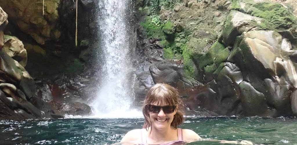 woman in swimming hole in front of Oropendola Waterfall