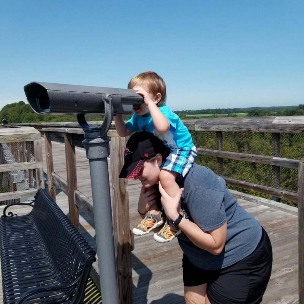 Toddler on woman's shoulder looking through binoculars on high bridge